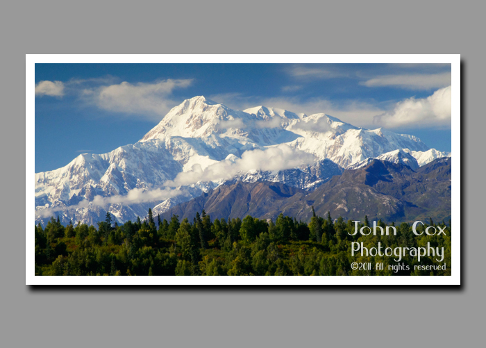 Clouds hover near a snow-dusted Denali in Denali National Park in Alaska.