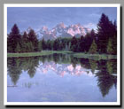 The Grand Tetons reflect in the crystalline waters of a small pond in Grand Teton National Park, Wyoming.