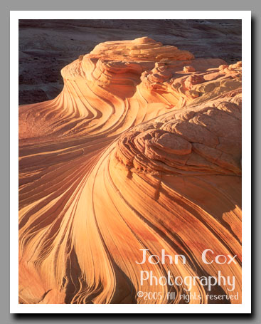 A sandstone wave glows brilliantly in the light of a setting sun in Coyote Buttes on the Utah-Arizona border.